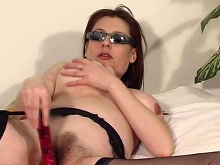 Mature redhead wearing nothing but her shades and stockings plays with her aged pussy paw